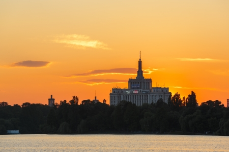 Sunset over House of the Free Press (still universally known as Casa Scanteii). View from the lake in Herastrau Park, Bucharest, Romania.  Editorial