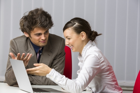 A team of two happy businesspeople sitting at desk and discussing and planning work in the office.