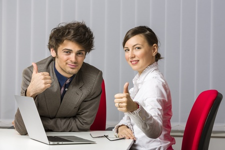 Cheerful successful business team giving the thums up at desk in the office. Stock Photo - 18493455