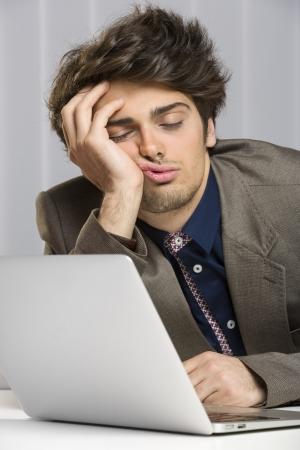 perezoso: Retrato de hombre de negocios con exceso de trabajo dormido delante de su ordenador port�til en el trabajo. Foto de archivo