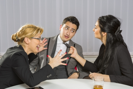 Two angry businesswomen harassing their guilty business partner in the office. Stock Photo