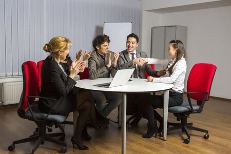 Group of cheerful business people acclaiming successful deal with the new woman partner.