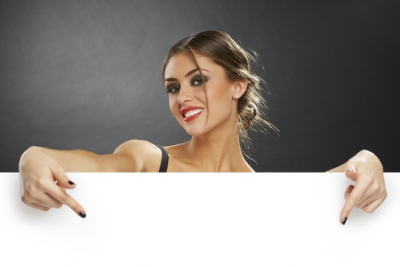 Excited young woman pointing her fingers down to the blank white advertising banner sign against dark background. photo