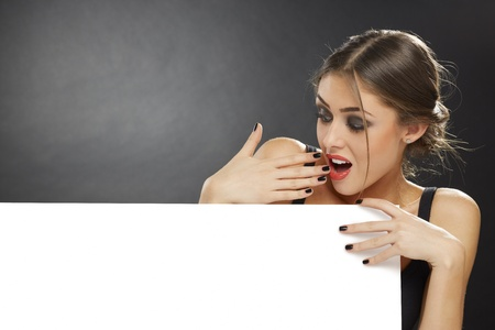 Portrait of a surprised young girl holding blank billboard against dark background. Stock Photo - 18824393