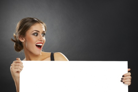 Excited joyful young woman holding blank white billboard against dark background.