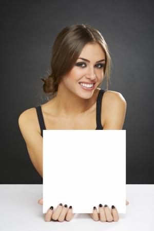 暗い背景上にブランクの看板を置く若いきれいな女性の肖像画。 写真素材