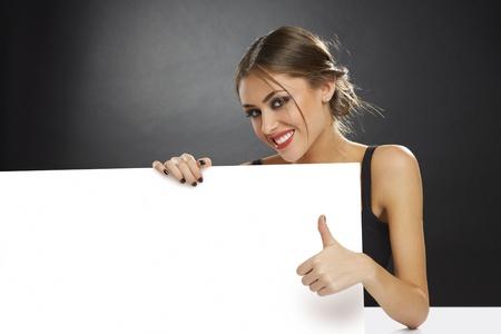 空白の白い広告バナーを保持し、暗い背景のサインを親指を与える若い女性の笑みを浮かべてください。 写真素材
