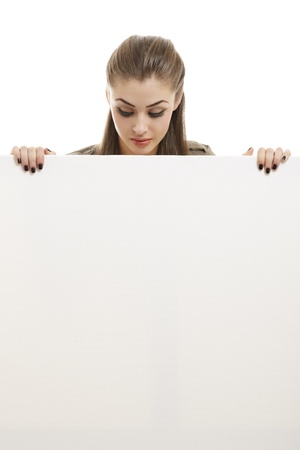 Portrait of beautiful happy business woman holding blank billboard and looking down on it. Isolated on white. Stock Photo