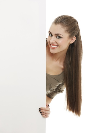 Portrait of smiling pretty woman peeking from behind vertical blank billboard sign over white background.