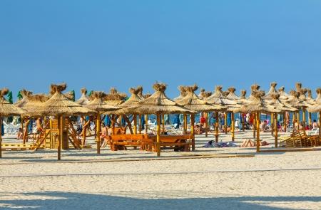 Mamaia, Rumänien - 5. August: Touristen sonnen-und Ruhezeiten unter Reed Sonnenschirme am Strand am 05. August 2011 in Mamaia, Rumänien. Mamaia ist Rumänien Standard-Bild - 19235802