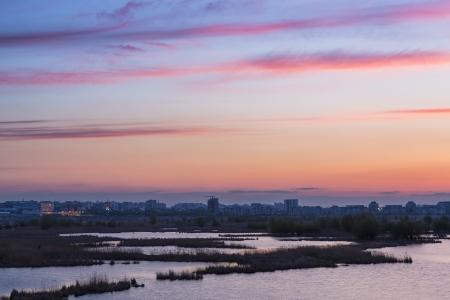 periphery: Purple sunset over south-eastern Bucharest suburbs near Vacaresti Lake, swamps
