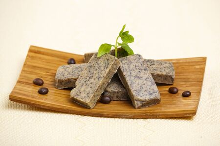 Heap of handmade flavored soap bars with coffee beans and green lavender leafs on wooden stand. photo