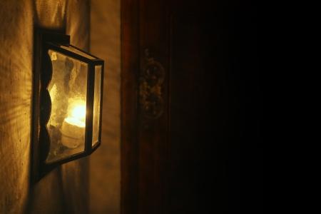 abatjour: Antica lampada da parete incandescente nella notte. Luci e modelli di ombre sul muro.