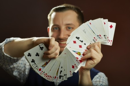 Happy skillful male magician performing playing cards jugglery on dark background