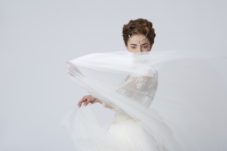 Excited female wearing wedding dress playing with the veil. Stock Photo