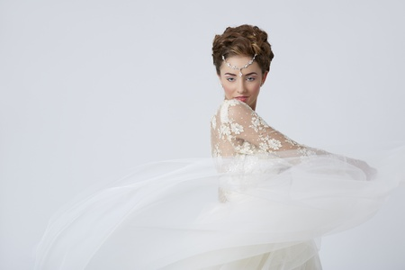 Portrait of beautiful female wearing wedding dress playing with the veil. photo