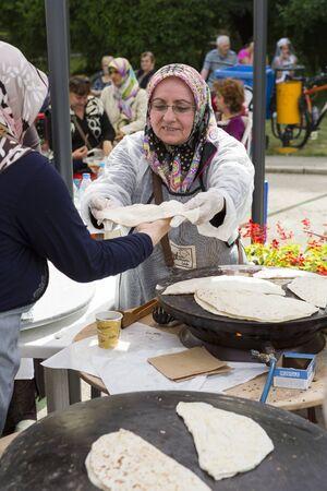 BUCHAREST, ROMANIA - MAY 17: Turkish women bake traditional suberek pie during the celebratory event Turkish Festival on May 17, 2013 in Bucharest, Romania. Editorial