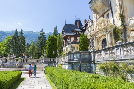 SINAIA, ROMANIA - JULY 24: Tourists walk the alleys of Peles garden on July 24, 2013 in Sinaia, Romania. Peles castle is the most visited museum in Romania with more than 300.000 tourists every year.