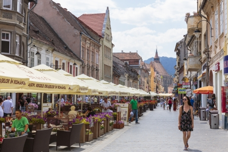 BRASOV, ROMANIA - JULY 14  Unidentified tourists walk or relax at cafes on crowded Republic Street on July 14, 2012 in Brasov, Romania  Brasov is the 7th largest city and the most visited in Romania