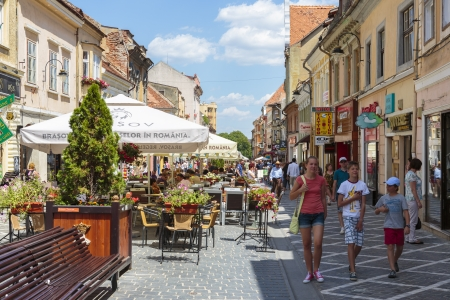 BRASOV, ROMANIA - JULY 25  Unidentified people stroll or relax at cafes on crowded Republic Street on July 25, 2013 in Brasov, Romania  Brasov is the 7th largest city and the most visited in Romania