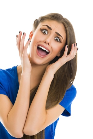 Surprised young woman with shocked facial expression screaming with mouth wide opened while gesturing with her hands against white background.