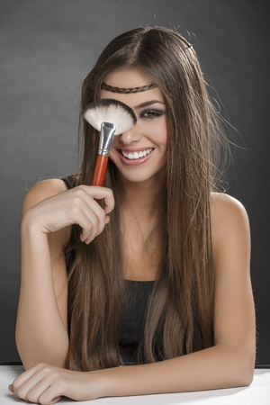 Young cheerful woman having fun while holding makeup brush against her eye over dark backgound. photo
