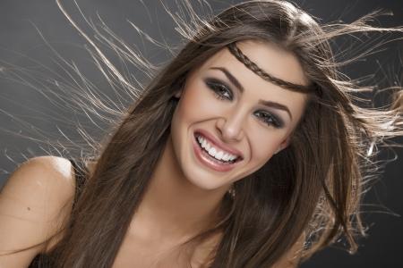 長い絹のような茶色の髪を吹くと幸せな笑顔美人の肖像画。メイクは、完璧な肌。髪の健康、髪型、髪のケア。