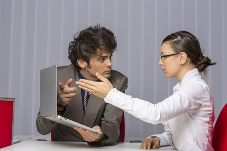enmity: Two irritated business partners arguing and gesturing while trying to solve business problems at work.