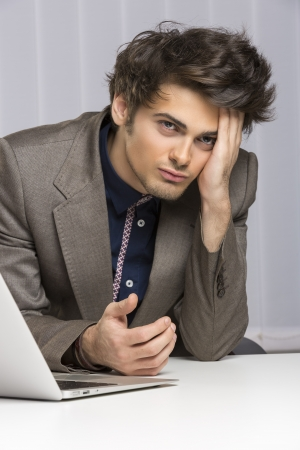 Stressed young businessman showing an attitude of failure, disappointment at work. Banking, insurance, law, sales. photo