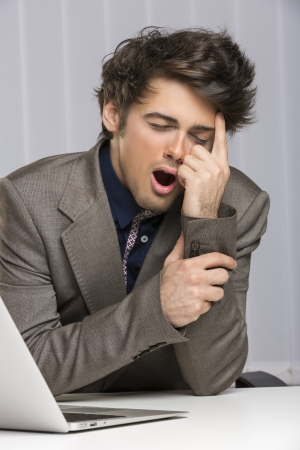 Portrait of young overworked exhausted businessman yawning at his desk at work. photo