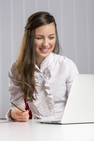 commerce communication: Happy smiling woman employee using laptop and internet for successful business communication. Banking, insurance, advertisement, commerce, consulting.