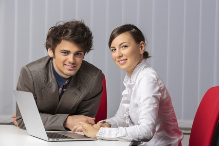 Two happy young business partners smiling at camera while working together on laptop in their office. photo