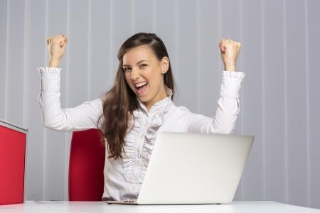 女性エグゼクティブ叫び、上げられた拳を食いしばってオフィスでラップトップの前に彼女のビジネスの勝利を祝って興奮。