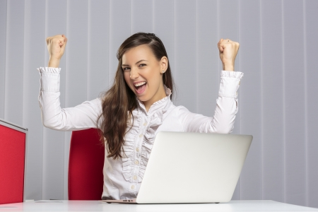 Excited female executive screaming and celebrating with raised clenched fists her business victory in front of laptop in the office. photo