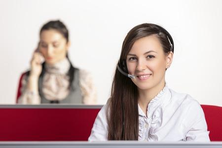 バック グラウンドで電話を取る女性の同僚との友好的な肯定的な女性顧客サービス担当者。