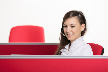 Smiling professional call center female agent having a helpful conversation with a customer via her headset. Red office workspace over bright background. Professional call center services. Stock Photo