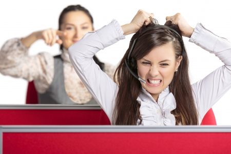 Angry frustrated call center female agent screaming and pulling her hair in rage with female colleague pointing at her from behind. Bad day at work. Stressful work environment.