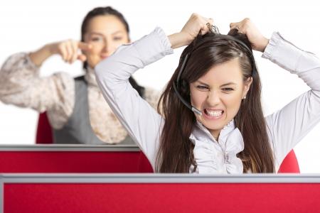 ambiente laboral: Call center agente femenino frustrado enojado gritando y tirando de su pelo de rabia con su colega femenina apuntando a ella por detr�s. Mal d�a en el trabajo. Ambiente de trabajo estresante.
