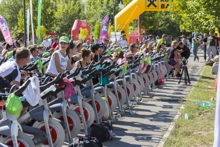 Group of people exercising their legs or doing cardio training during a public cycling marathon on stationary bikes on 15 09 2013 in Bucharest, Romania