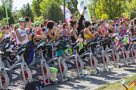 Group of men and women cheering after successfully finishing their exhausting cardio exercise during a public cycling marathon on stationary bicycles on 15 09 2013 in Bucharest, Romania