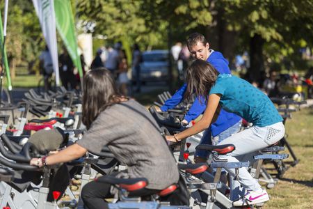 Unidentified group of young people exercising their legs on stationary bikes during a public cycling festival on 15 09 2013 in Bucharest, Romania