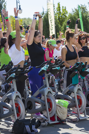 Group of women stretching using stationary bycicles for cardio training during a public cycling exercise on stationary bikes on 15.09.2013 in Bucharest, Romania.