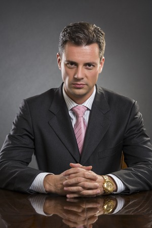 Portrait of successful handsome well-dressed young businessman looking confidently at the camera in his office over dark background. Smart people.