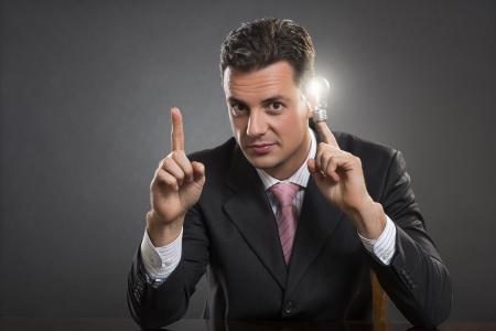 肯定的なスマート コンサルタントで明るい電球を保持しているが、寺暗い灰色の背景上にある彼の人差し指を指します。スマートなビジネス戦略の