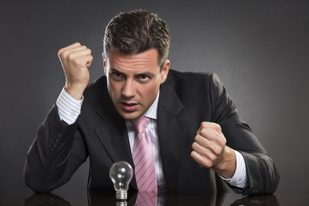 seeking solution: Portrait of angry businessman with clenched fists seeking desperately for smart business solution over dark background. Stock Photo