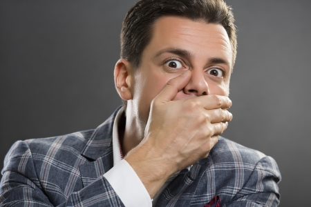 灰色の背景を自分の手で彼の口を覆うスーツを着ていることを恐れての実業家の肖像画。
