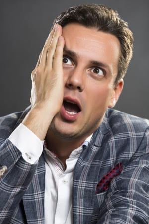 ハンサムな若い実業家開口と灰色の背景の上探している大きな目でショックを受けた式で彼の顔に彼の手を握ってします。 写真素材