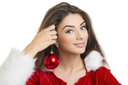 flirtatious: Portrait of excited flirtatious young woman in Santa Claus outfit holding red Christmas ball as earring over white background. Stock Photo