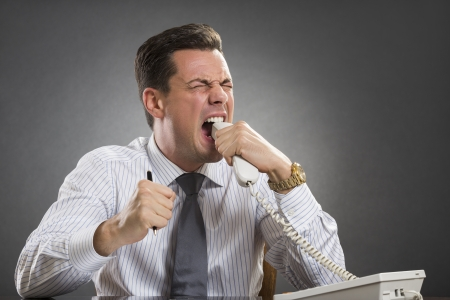 enraged: Furious frustrated executive wearing white shirt and tie biting phone receiver while showing an enraged face grimace over grey . Stock Photo