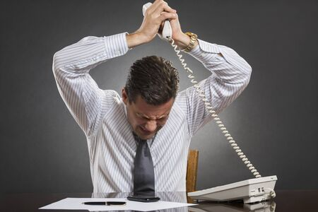 temper: Nervous frustrated businessman wearing white shirt and tie losing temper control after receiving bad news on the phone over grey .